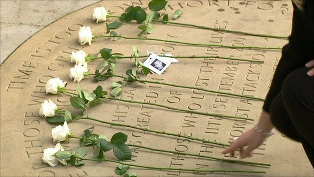 Woman placing rose on memorial plaque in Grosvenor Square