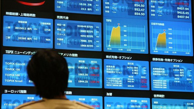 Trader looking at markets boards in Tokyo