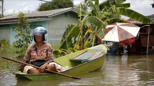 A woman wears a helmet as she maneuvers a small boat through a flooded area in Ayutthaya province