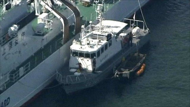 Refugees' small wooden boat tied to Japanese coastguard boat, tethered to large coastguard ship