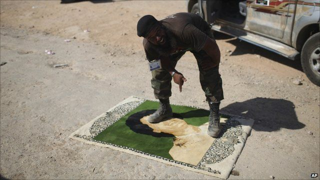 Anti-Gaddafi fighter standing on carpet showing Colonel Gaddafi's face