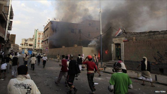 Anti-government protesters walk past a government building on fire during clashes in Sanaa