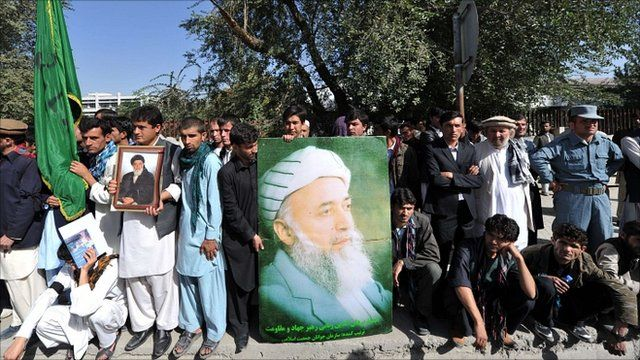 Supporters of former President Burhanuddin Rabbani hold a poster of his image outside the compound of his home in Kabul