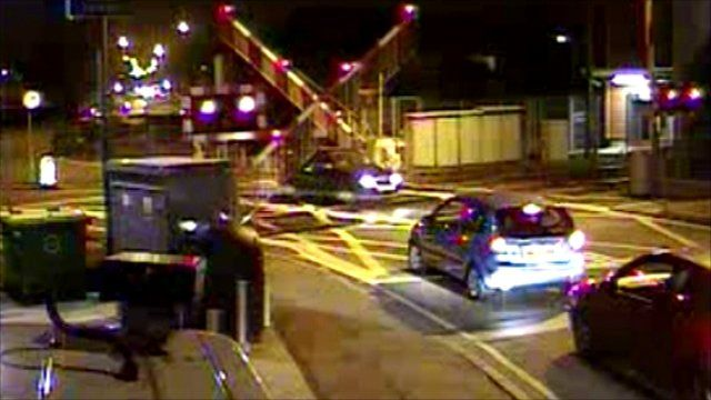Car driving under level crossing barriers