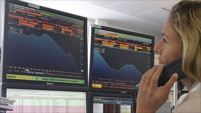 A stock trader checks out graphs showing activity of the euro currency against the US dollar