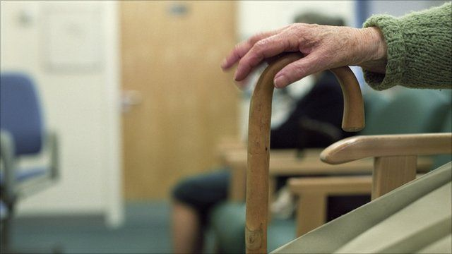 Elderly woman resting her hand on walking stick