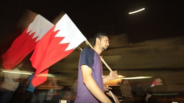 Bahraini anti-government protesters walk with national flag