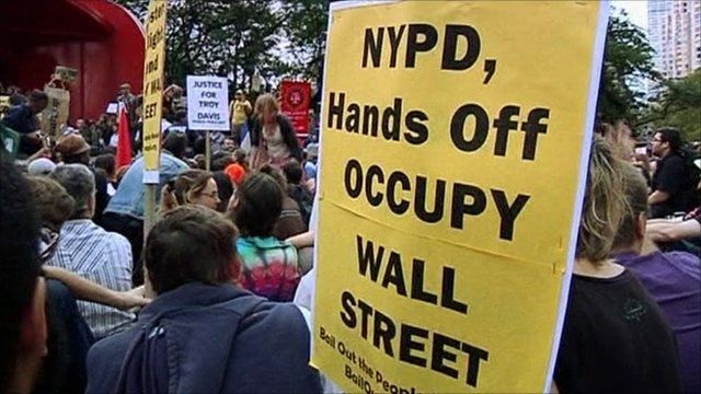 Protesters holding placards at Occupy Wall Street demonstration