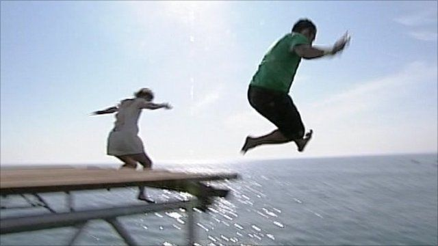 People jump into the sea