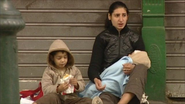 A woman begging with two children on the streets of Athens