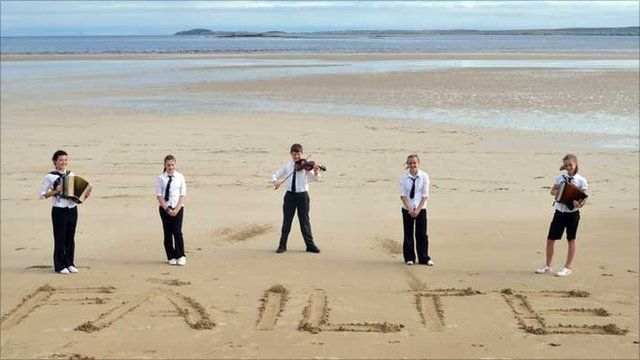Children from a school on Lewis stand on a beach (Picture: Royal National Mod)