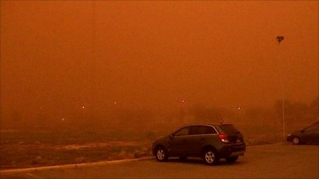 Car parked in foreground as dustcloud sweeps through Lubbock, Texas