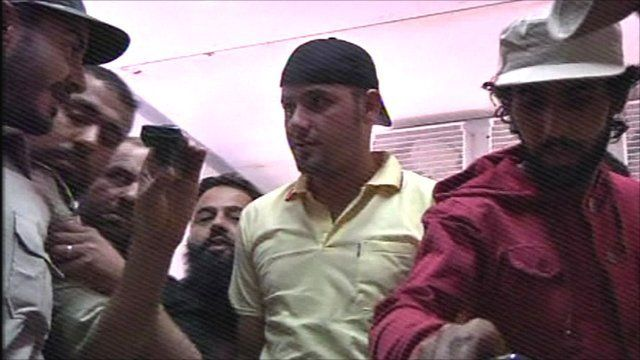 Peopel crowd round Gaddafi's body