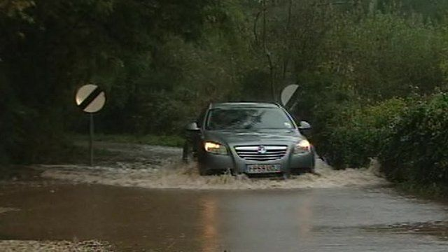Car driving through several inches of water on road in south Wales