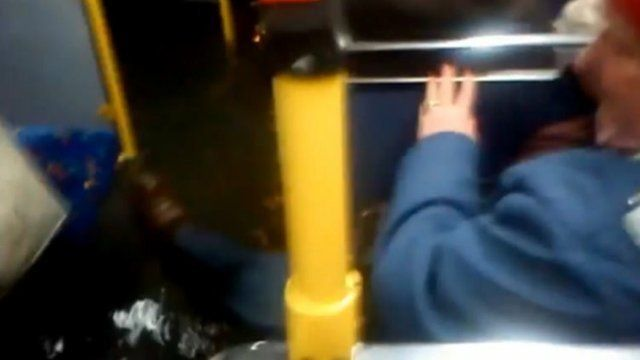 Bus passenger lifts foot away from floodwater