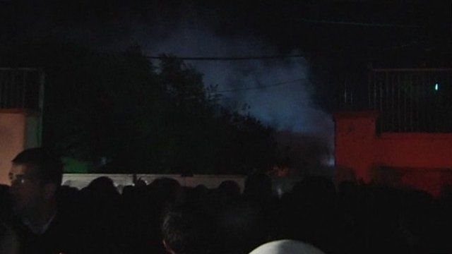 People gathered outside the prison in Van as smoke is seen rising inside the compound
