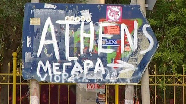Graffiti sign pointing towards Athens