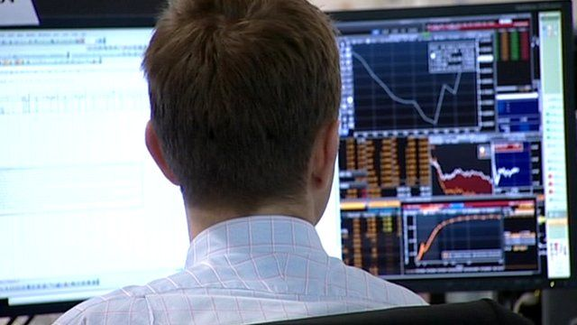Worker in the City looks at figures and graphs on screen