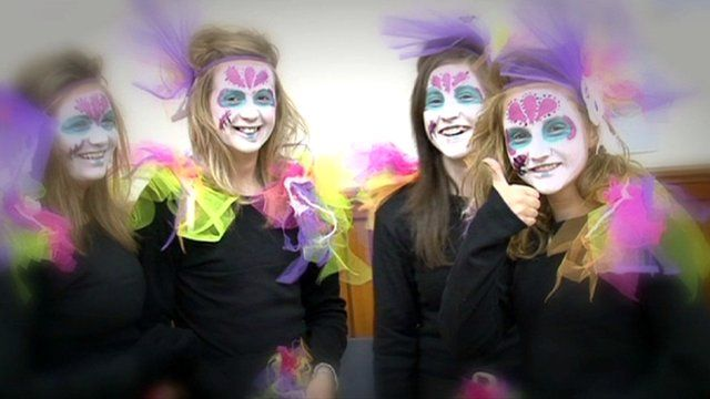 Girls with painted faces and wearing costumes