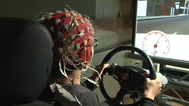 A researcher's brain signals are monitored as he uses a driving simulator.