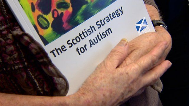 Elderly lady holding Scottish Strategy for Autism report