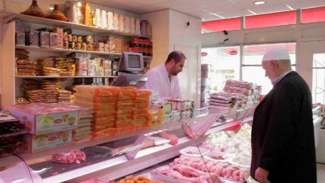 Halal butcher serving customer