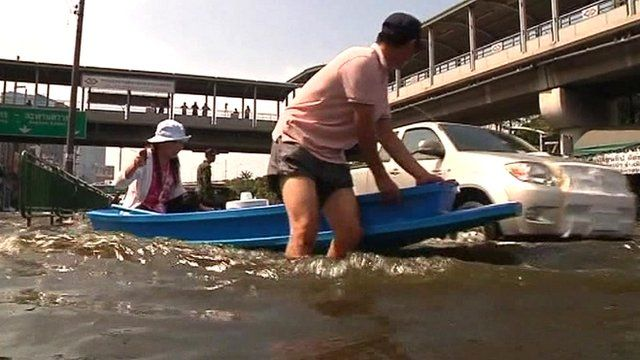 People wading through floods in Thailand