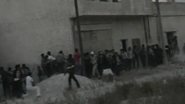 Protesters take cover from fire in Syria