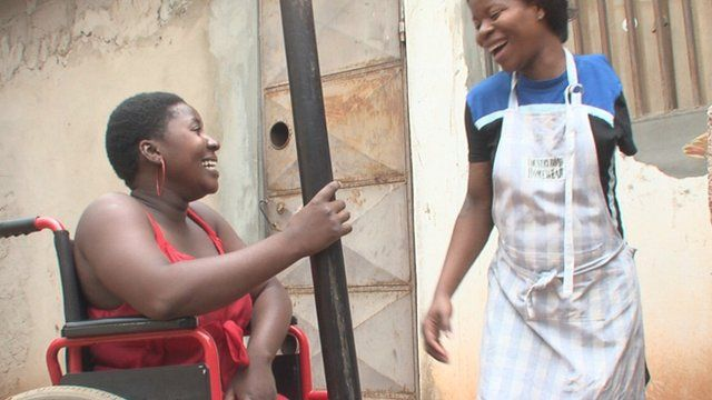 Mariana Tembe (l) and Victoria Massingue (r) laughing as they prepare food together