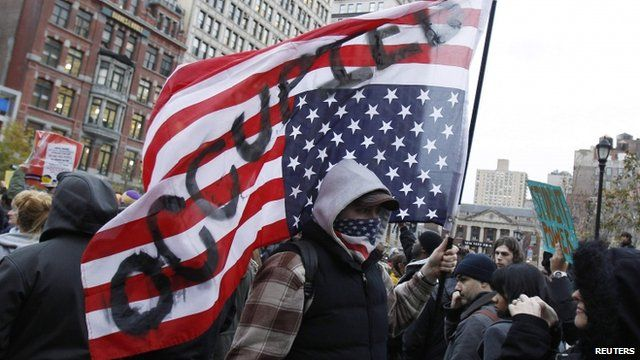 """Occupy Wall Street protester carrying upside down US flag with """"occupied"""" written on it"""