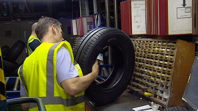 Men checking tyres in a factory