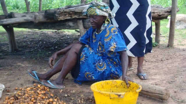 Women in Africa with nuts and a bucket