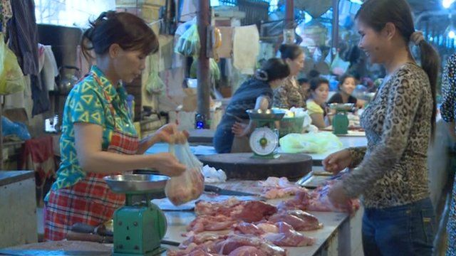 A customer buying meat in a market in Vietnam