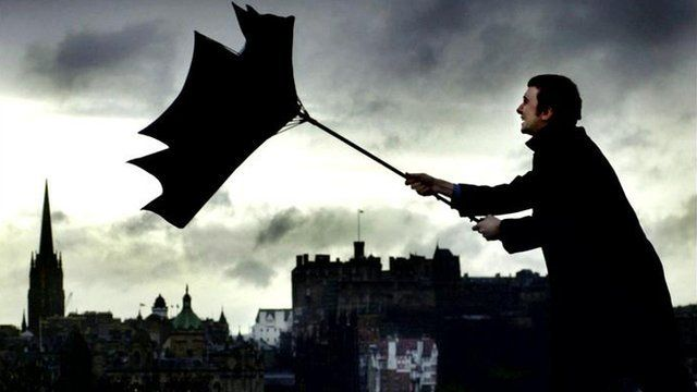 A man tries to control his umbrella in strong winds and heavy rain while walking past Edinburgh Castle.
