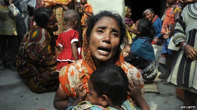 Relatives of victims mourn near the dead body of their kin in Sangram Nagar village