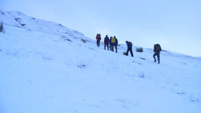 Walkers in snow covered Brecon Beacons