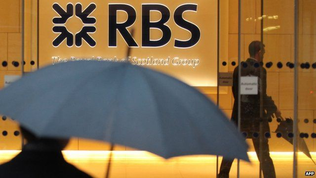Men with umbrellas outside branch of RBS