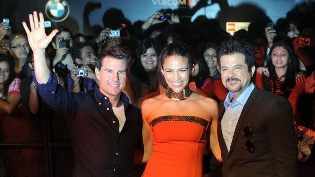 Tom Cruise (L) poses with co-actors Paula Patton (C) and Anil Kapoor (R)