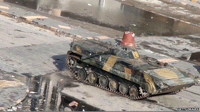 Syrian tank driving through the city of Homs