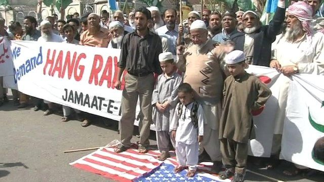Pakistani protesters standing on US flag