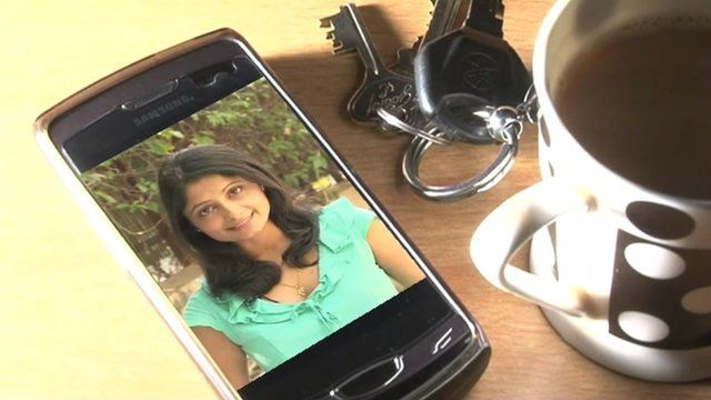 The BBC's Rajini Vaidyanathan's image on a smartphone next to some keys and a cup of tea