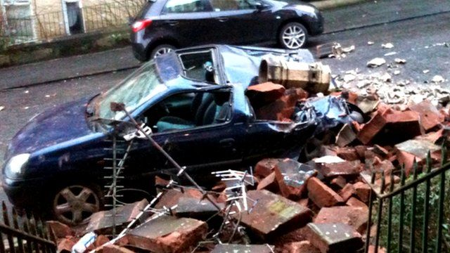 A collapsed chimney crushes a car in the street