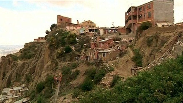 Abandoned residential buildings on a partially destroyed hillside