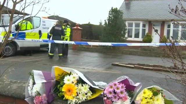 Police cordon and flowers at the scene of the fire