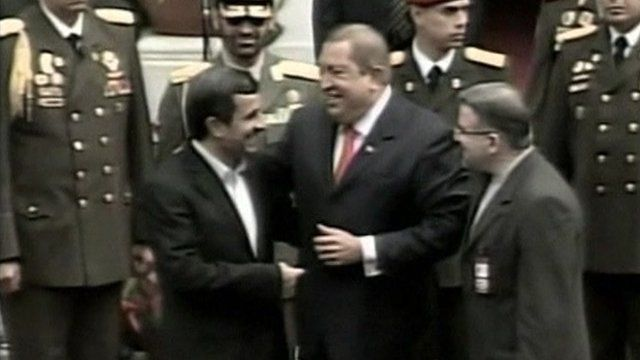 Mahmoud Ahmadinejad and Hugo Chavez laugh together.