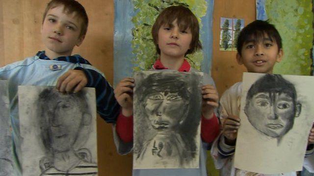 Children holding self-portraits