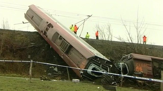Carriages from the Virgin Pendolino train lying on their sides on the embankment