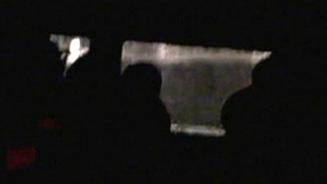 Silhouettes of passengers in lifeboat
