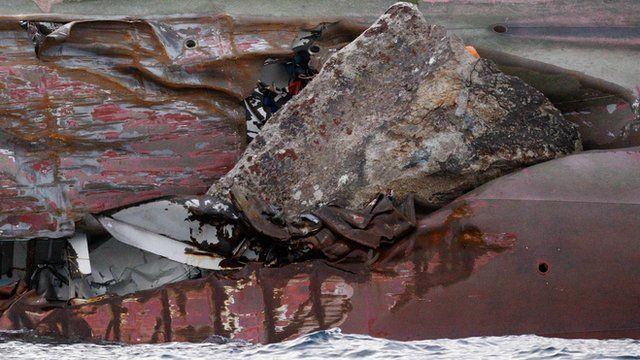 Rock protrudes from large gash in the hull of the capsized Costa Concordia cruise liner