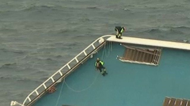 Rescue workers climb the ship using ropes